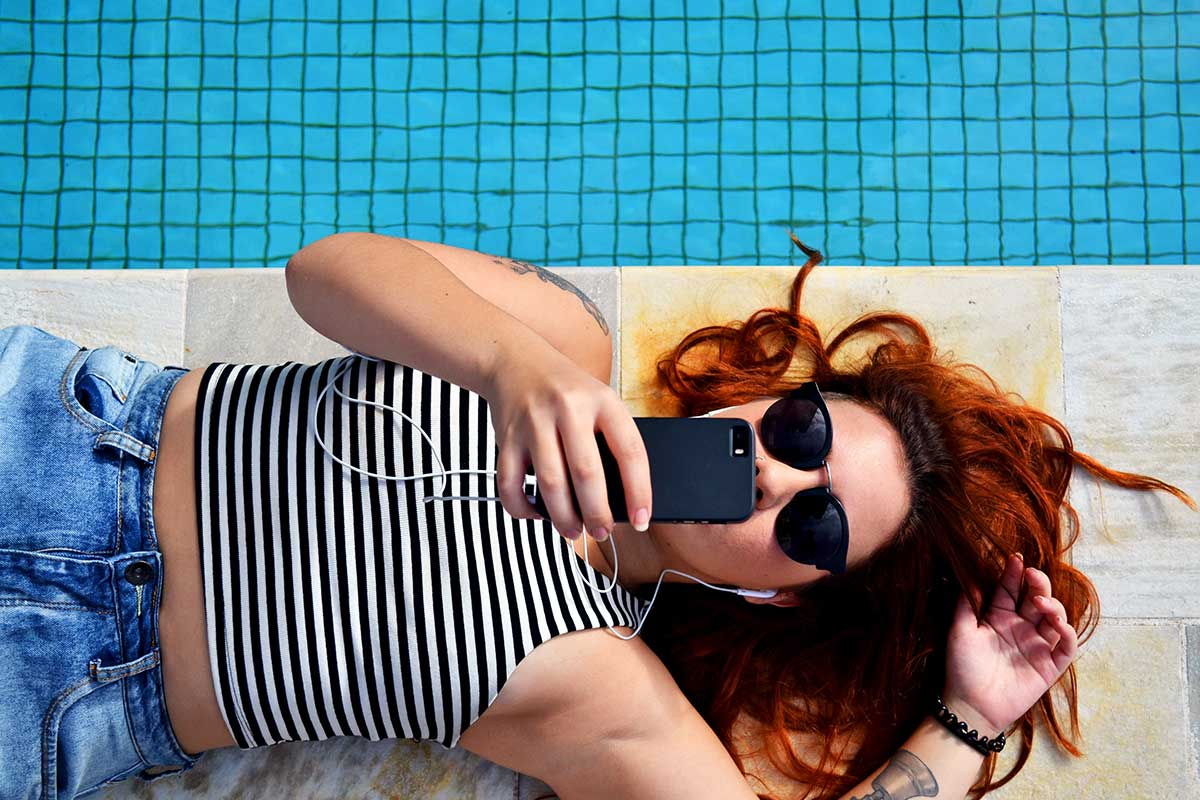 woman laying down next to swimming pool using her mobile phone to share content with friends