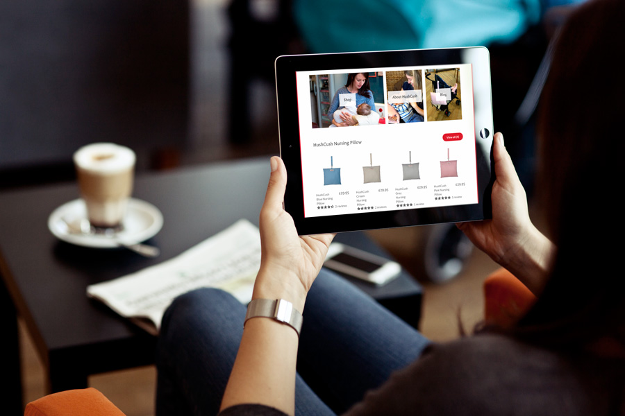 woman viewing the HushCush Shopify responsive web design on a iPad